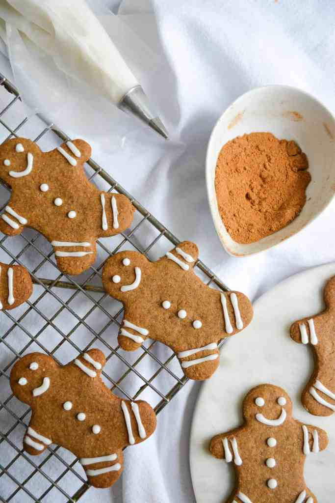 Decorated gingerbread cookies on a wire rack with a jar full of gingerbread spices