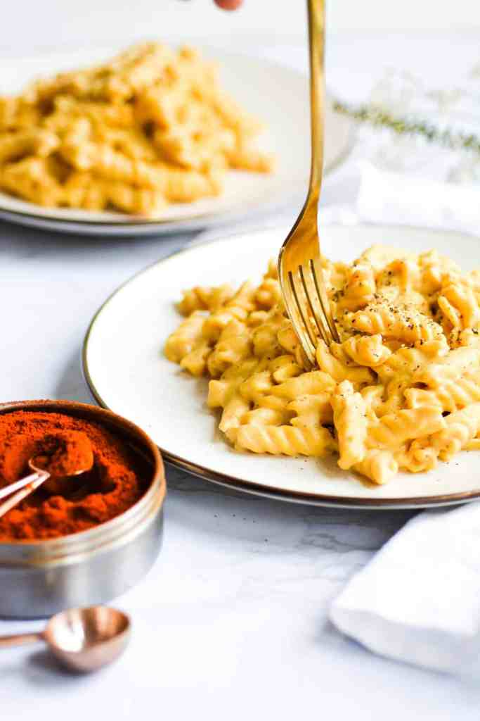 2 plates of stovetop mac and cheese with a gold fork