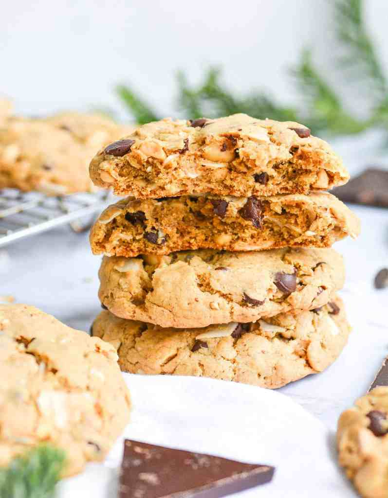 A stack of easy vegan cookies with one broken in half to expose the interior of the cookie