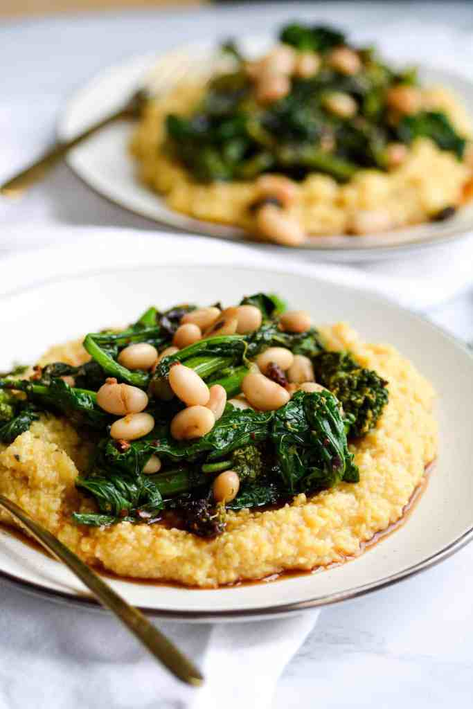 Close up of a plate of polenta with broccoli rabe and white beans