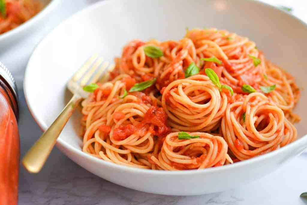 Lanscape of spaghetti with marinara sauce in a white bowl topped with basil