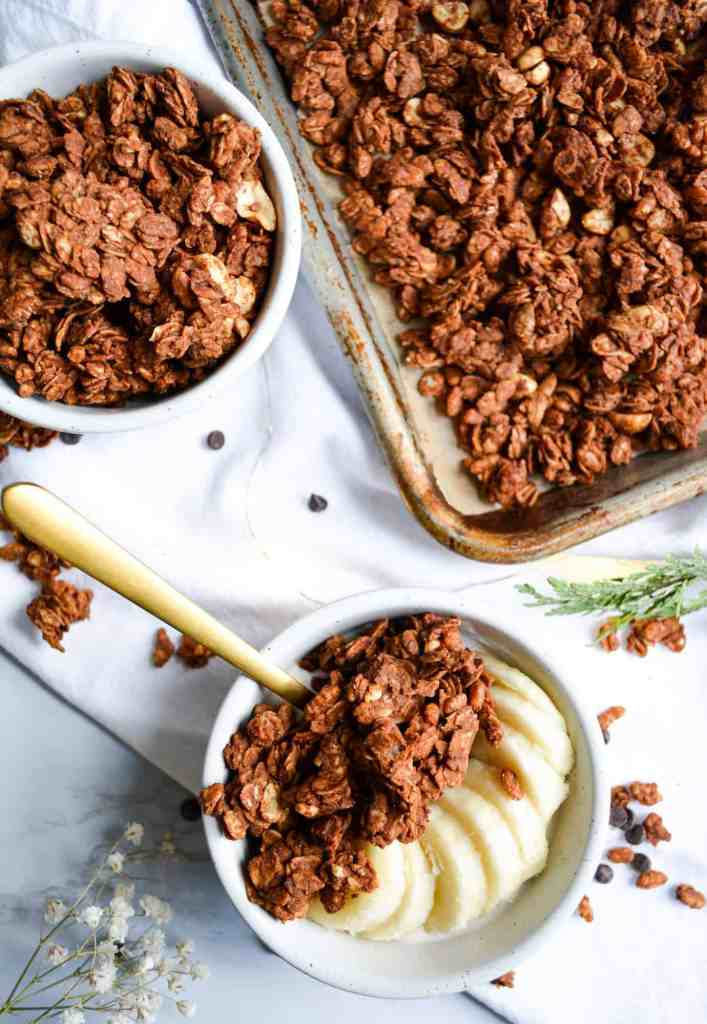 two ramekins of granola and a sheet pan with granola on it