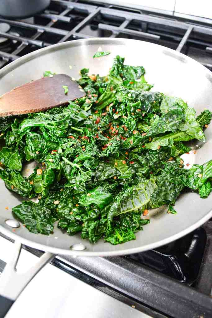 Kale in a skillet with crushed red pepper flake on top