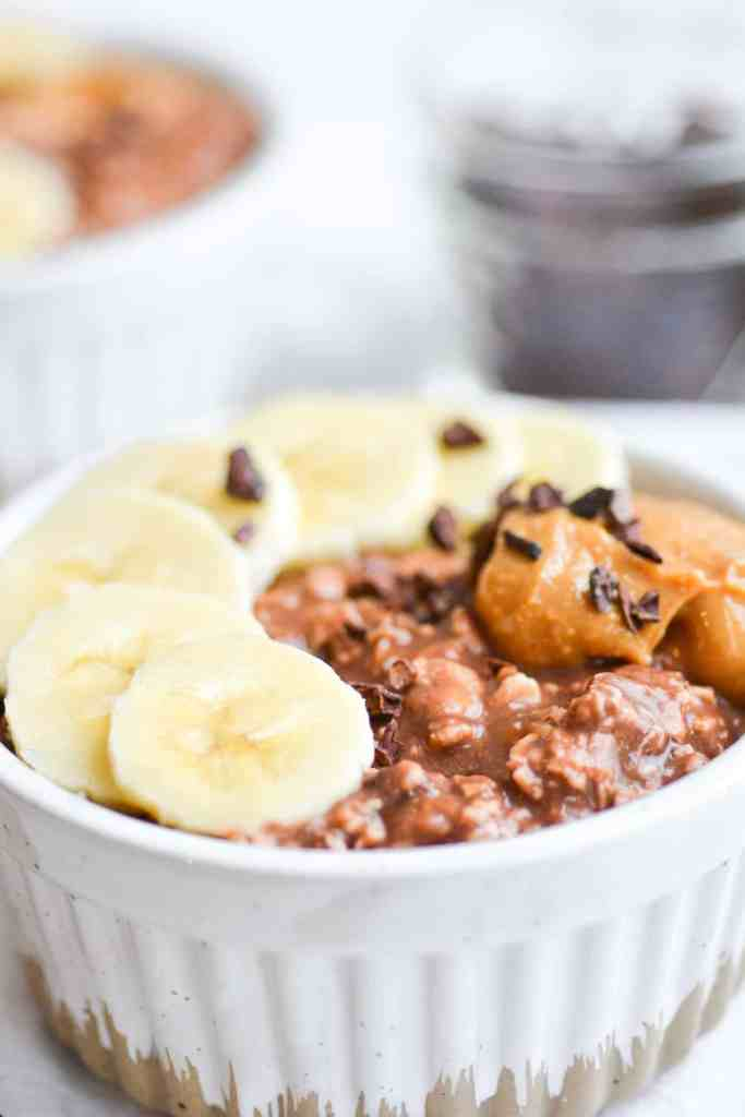 Close up of oats in a ramekin topped with banana