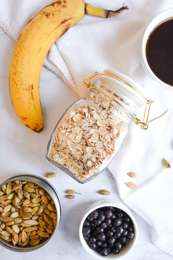 Ingredients for pancakes on a marble board- oats, a banana, cardamom pods and blueberries
