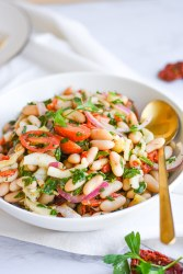Bowl of white bean salad with a serving spoon