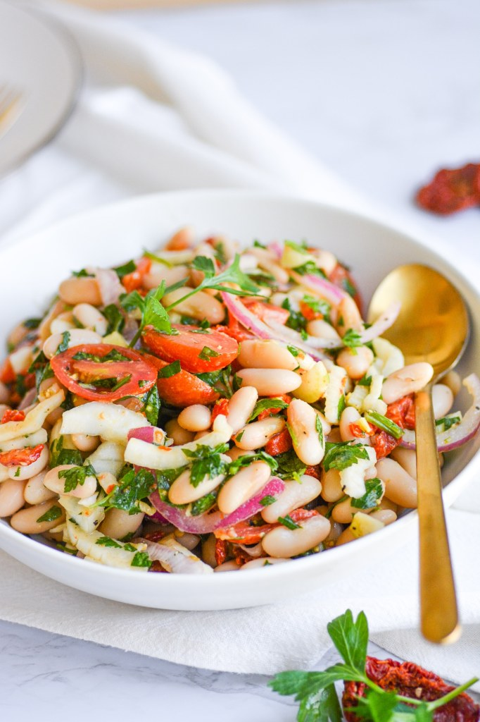 Bowl of vegan tuscan bean salad with a serving spoon