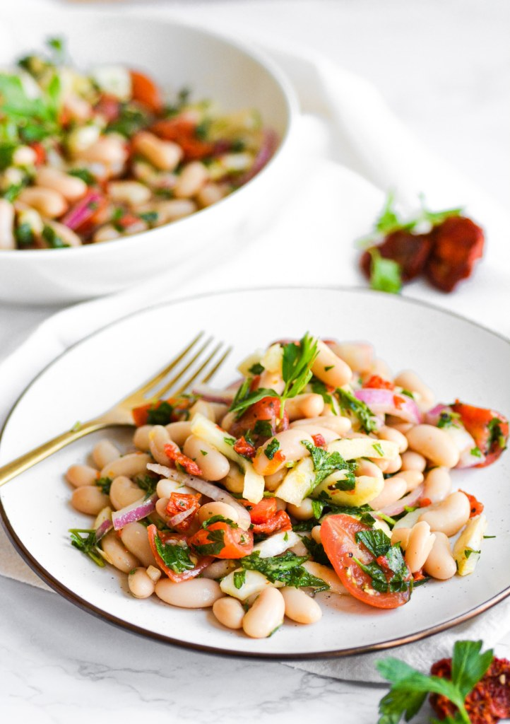 Two plates of vegan tuscan bean salad full of cannellini beans and tomatoes on a marble board