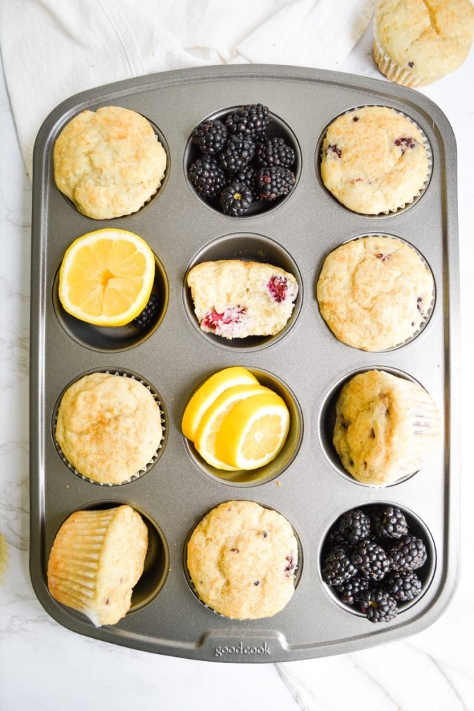 A muffin tin filled with vegan blackberry muffins, lemon slices and blackberries
