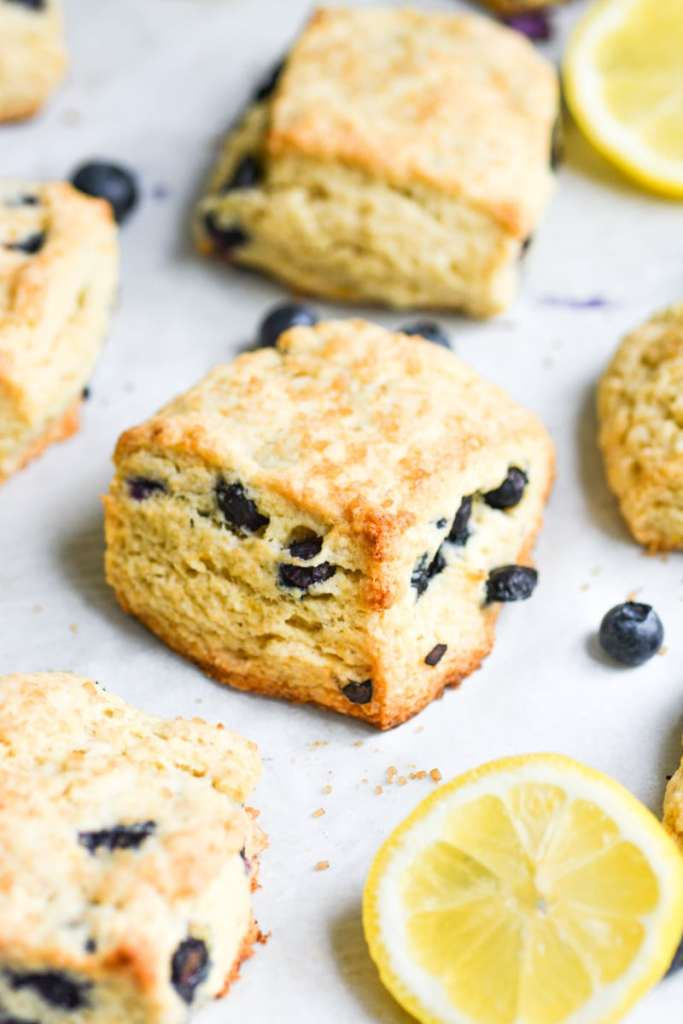 close up of blueberry scone on a baking sheet with a lemon slice