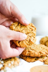 hands breaking apart an eggless and dairy free oatmeal cookie