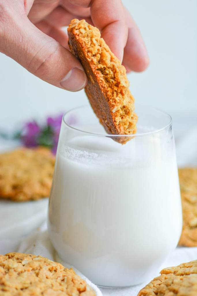 Hand dunking a Vegan Oatmeal peanut butter cookie into a glass of milk