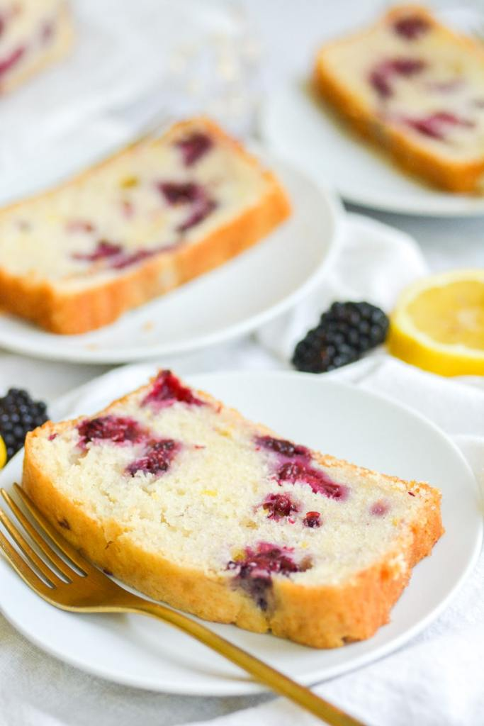 Close up of blueberry lemon bread slice on a white plate