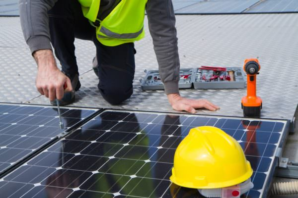 Man working on a solar renewable energy panel