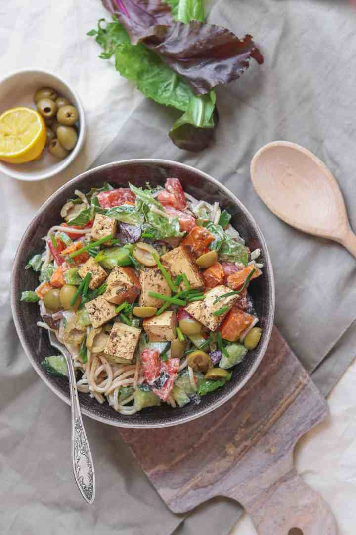 Overhead photograph of a vegan spaghetti salad with colourful vegetables, green olives, tofu and a tahini-based dressing