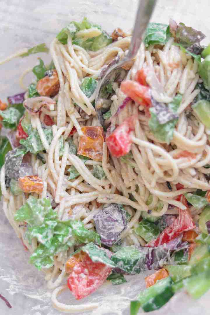 Closeup of vegan spaghetti with vegetables and a tahini dressing in a mixing bowl