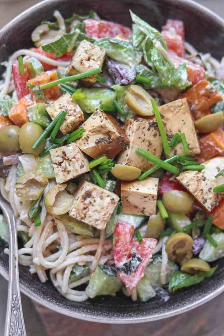 Closeup of cold pasta salad with tofu, vegetables, green olives and a tahini dressing in a large serving bowl