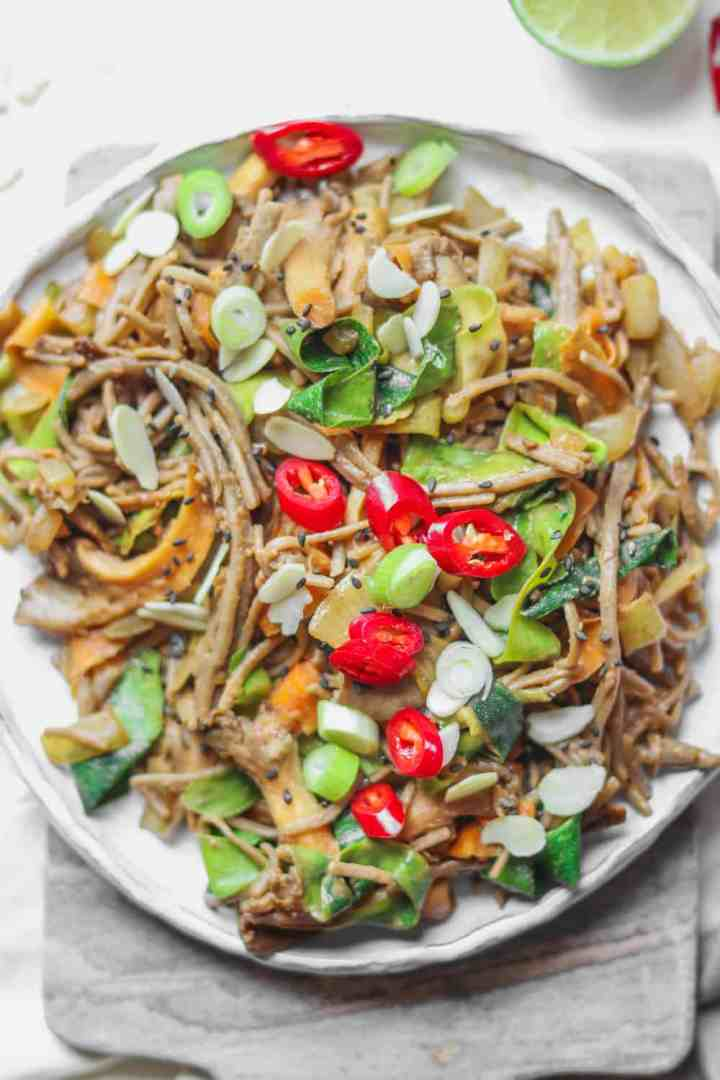 White plate with stir-fried soba noodles and vegetables
