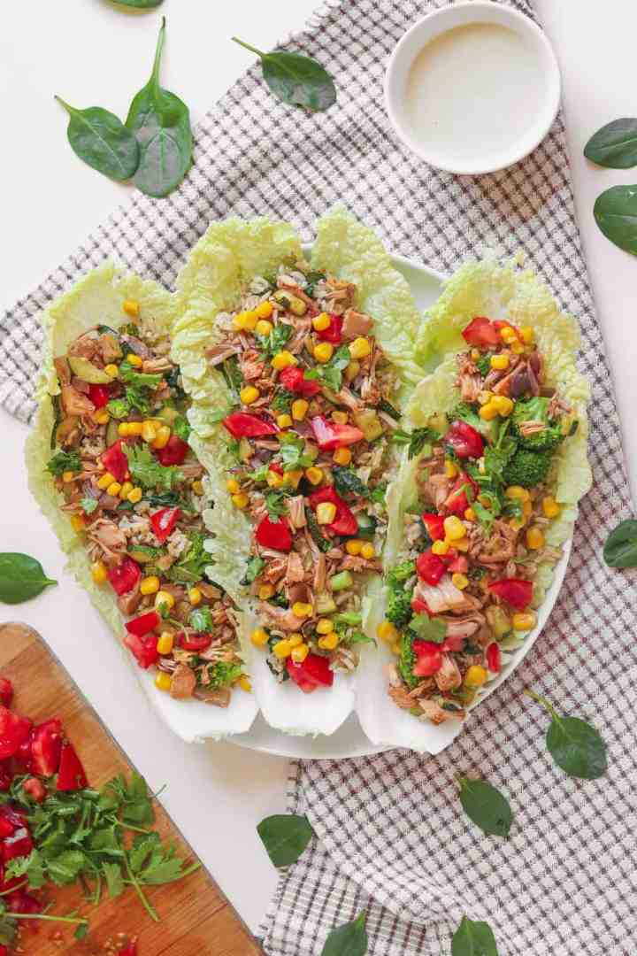 Brown rice and jackfruit vegan lettuce wraps on a plate with an oil-free cashew dressing standing nearby
