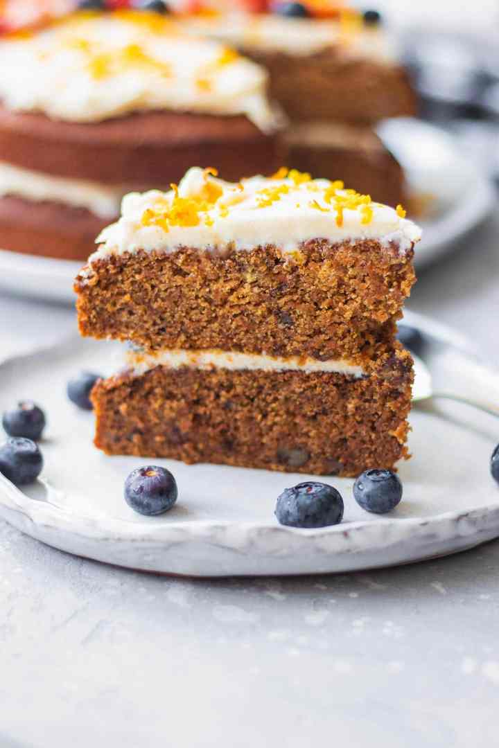Slice of vegan carrot cake with white frosting on a plate