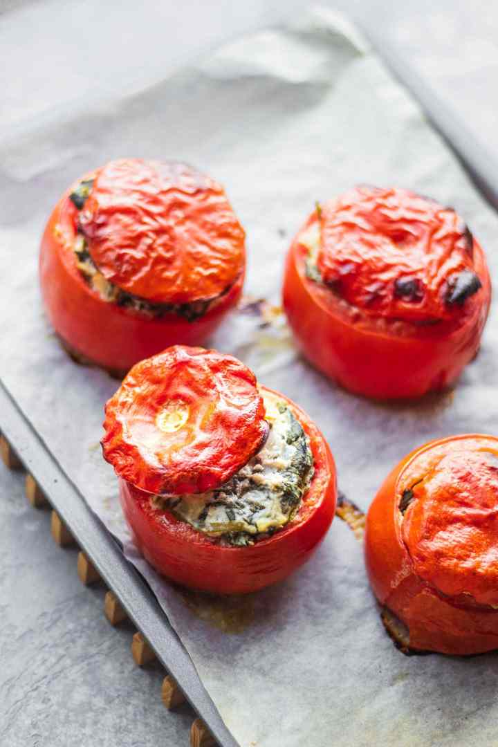 Vegan stuffed tomatoes with creamed spinach on a baking tray