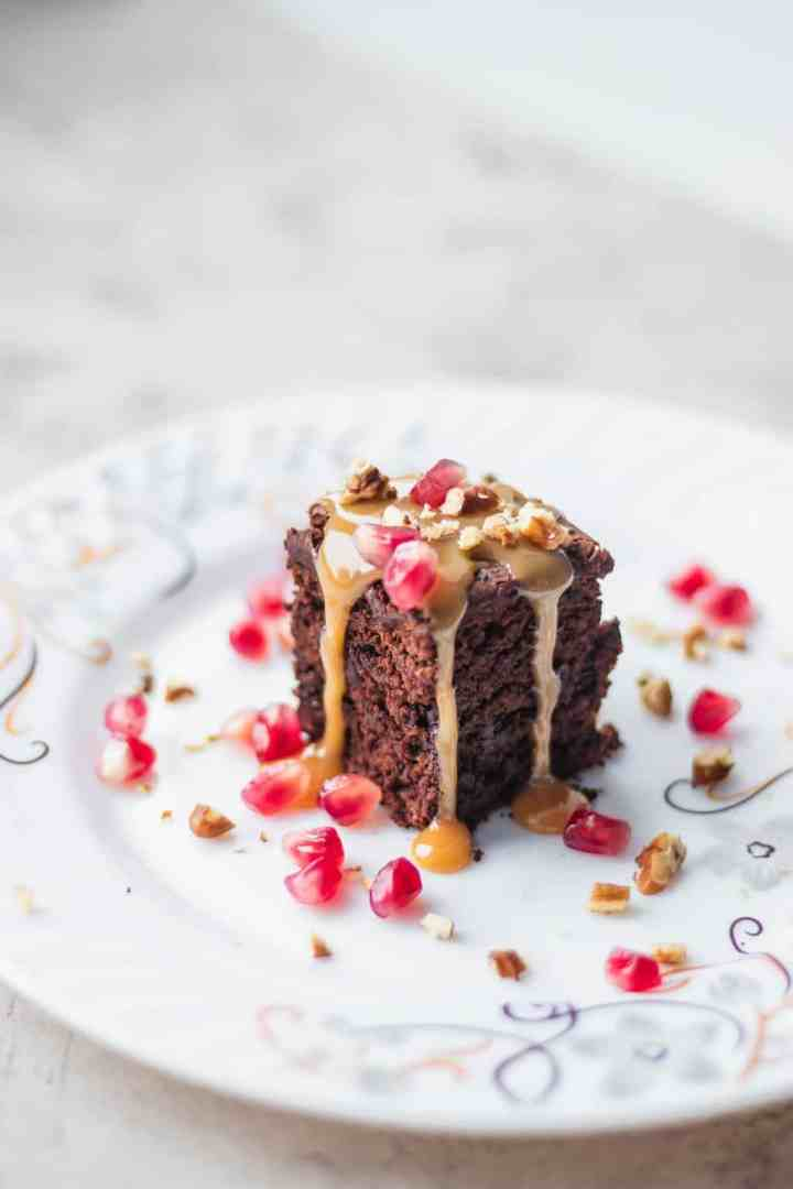 Brownie with salted caramel sauce and pomegranate seeds on a white plate