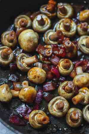 Mushrooms and onions in a frying pan