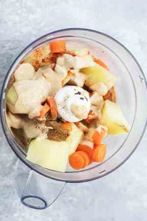 Potatoes and carrots with spices in a food processor