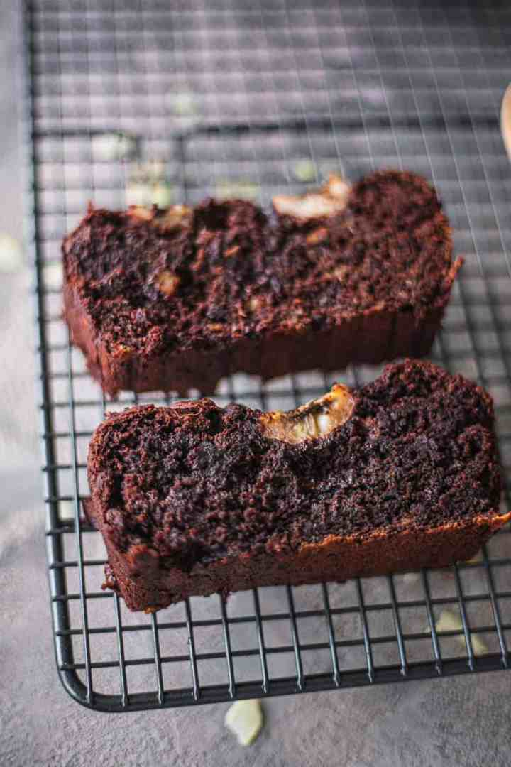 Two slices of chocolate banana bread on a cooling rack