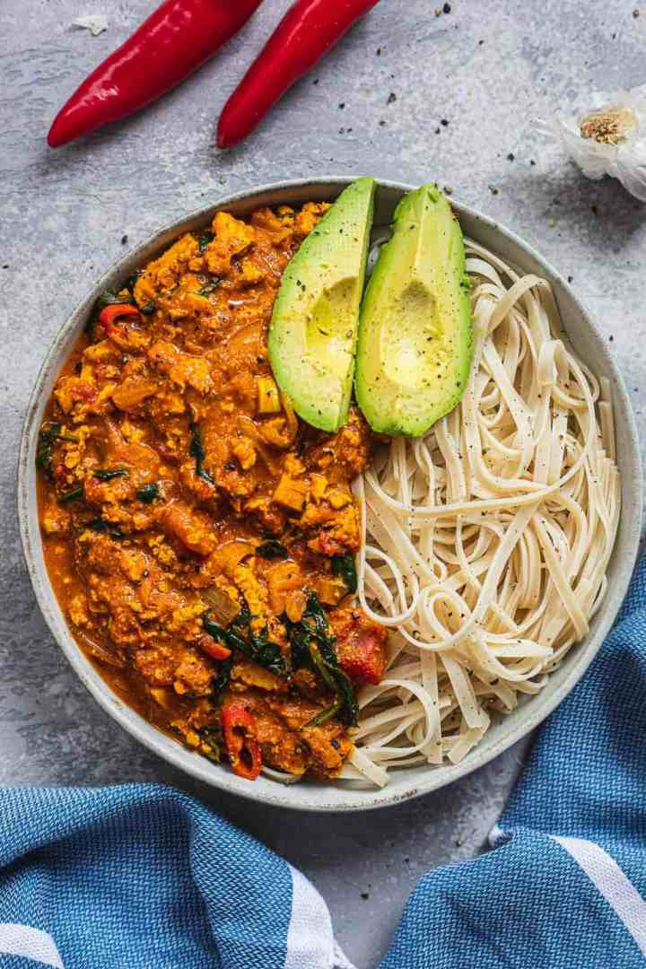 Curry with spinach and tofu in a bowl with noodles and avocado
