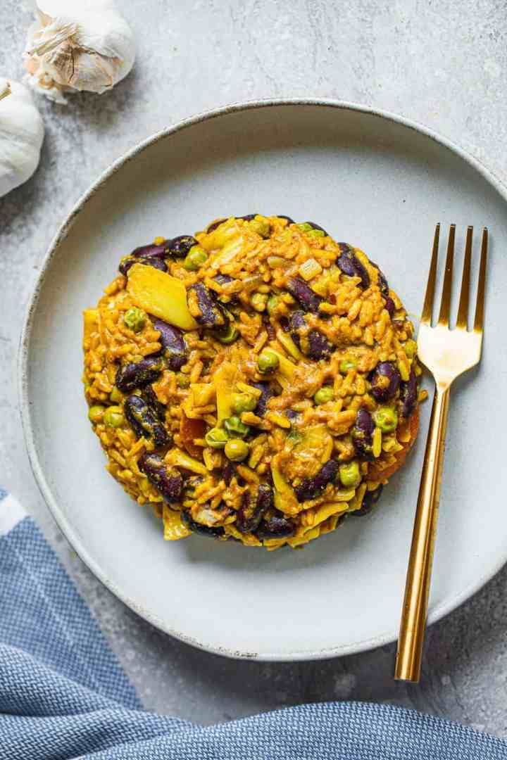 Curried rice and beans on a white plate