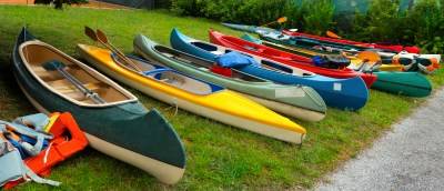 Group of canoes and kayaks on a green grass