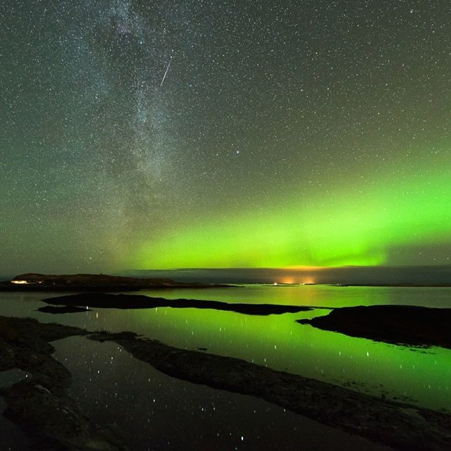Beautiful green aurora along horizon reflected in shallow water, with a meteor trail above it.