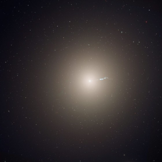 An elliptical galaxy shown as a central bright light with a gradually decreasing brightness the further away you are from the center.  From the center, a bluish light radiates to the right.