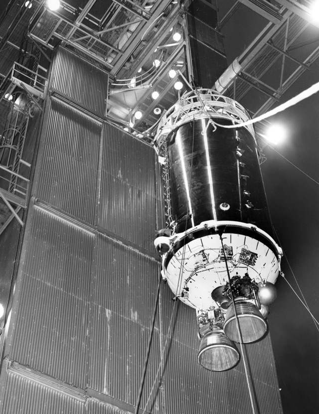 Cylinder with two rockets on the end hanging from a crane, viewed from below.