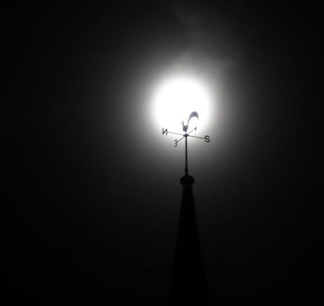 Harvest Moon behind a weather vane with four arms and a flat metal rooster on top.