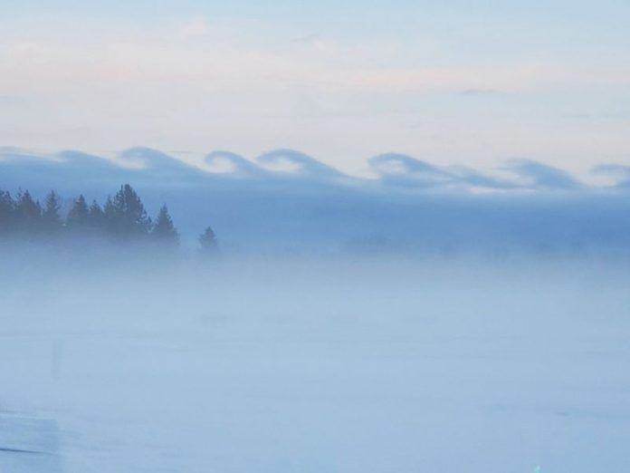 Line of clouds looking like side view of row of ocean breakers.