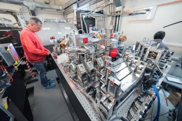 Large complex machine in lab with man standing next to it.