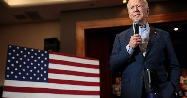The white-haired man in the suit, holding a microphone, is standing in front of a huge American flag.