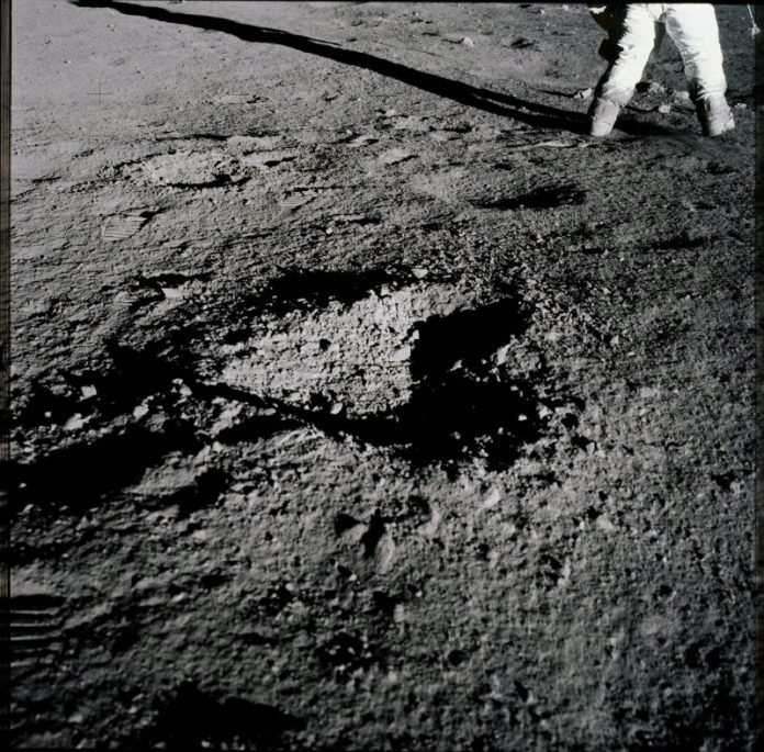 Rocky gray ground with a shallow hole the shape of a heart, space-suited legs.