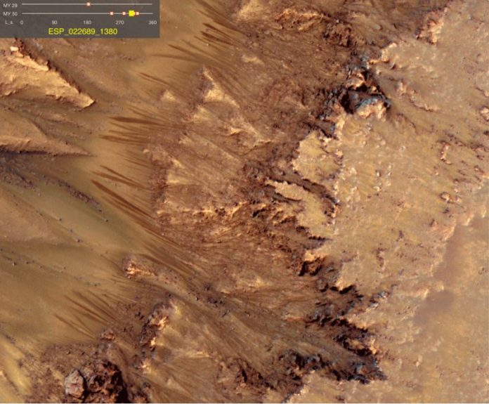 Long, thin, parallel dark streaks on reddish rocky slope.