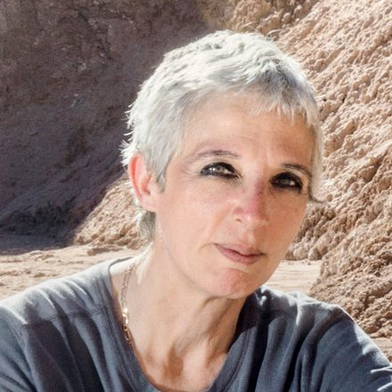 Woman with short grey hair and black eye makeup.