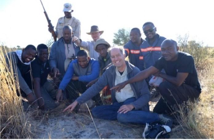 एक छोटी चट्टान की ओर इशारा करते 10 लोगों का समूह।