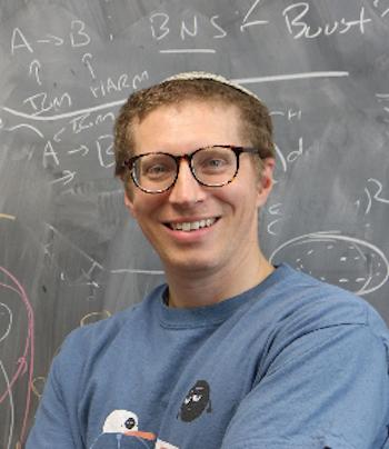 चॉकबोर्ड के सामने चश्मा लगाकर मुस्कुराता हुआ आदमी।