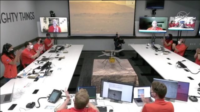 Mars helicopter first flight, as seen from the control room at NASA/JPL, with applauding red-dressed peple seated around a U-shaped table, with multiple monitors and a model of the helicopter in the center.