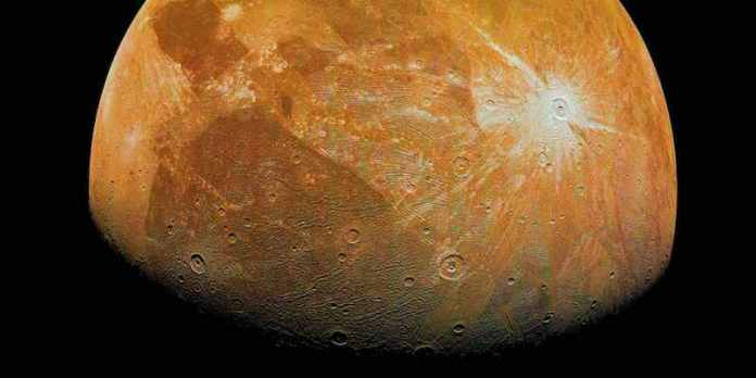 Orangish moon-like body with craters and bright and dark patches.