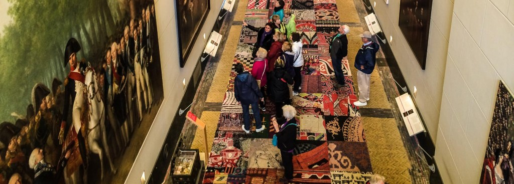 Picture of people standing on multi-colored floor looking at pictures.