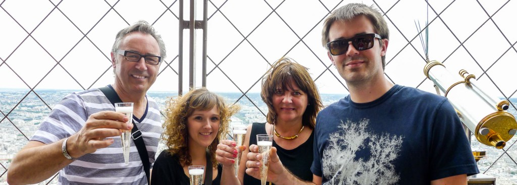 Picture of four people having champagne on the Eiffel Tower.