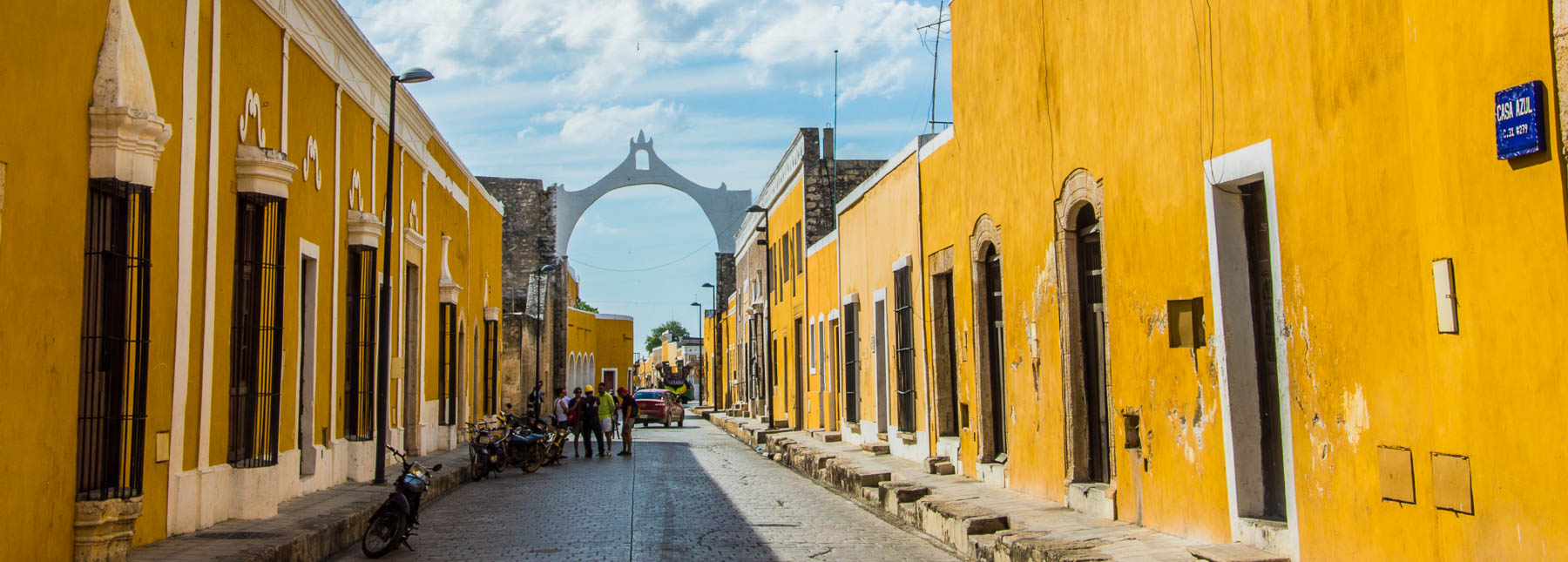 A view of an Izamal street with yellow painted houses on the Yucatan Road Trip.