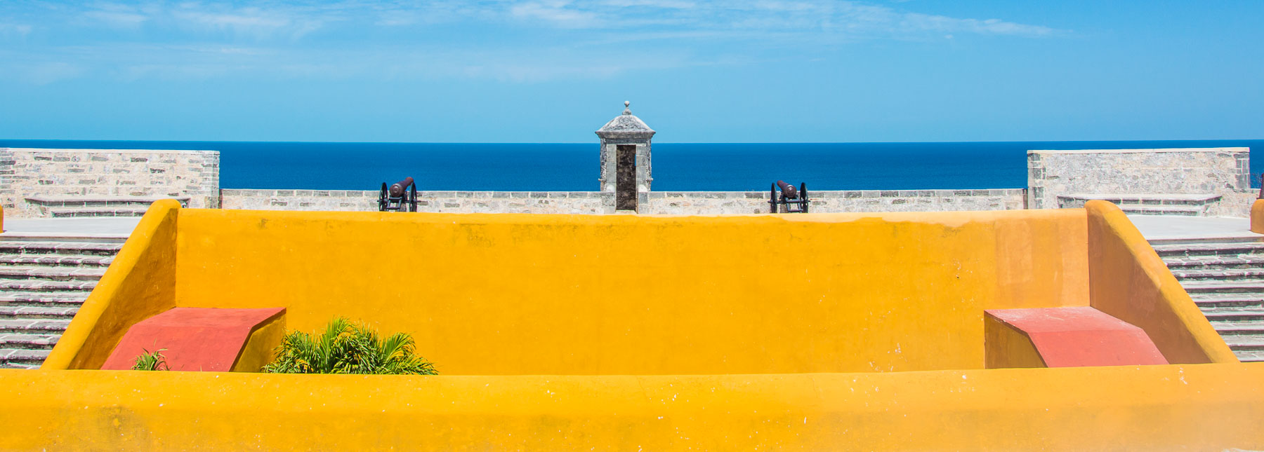 Picture of a bright yellow fort with cannons.